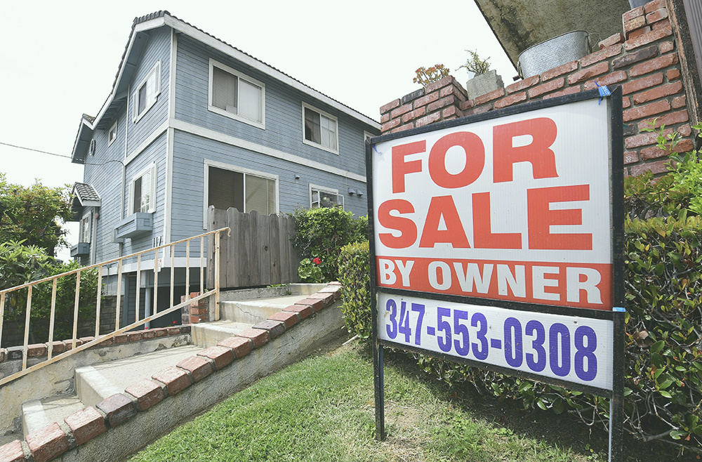 "A ""For Sale by Owner"" sign is posted in front of property in Monterey Park, California, last year. After record lows throughout 2020 and to start this year, mortgage rates are expected to increase this year."