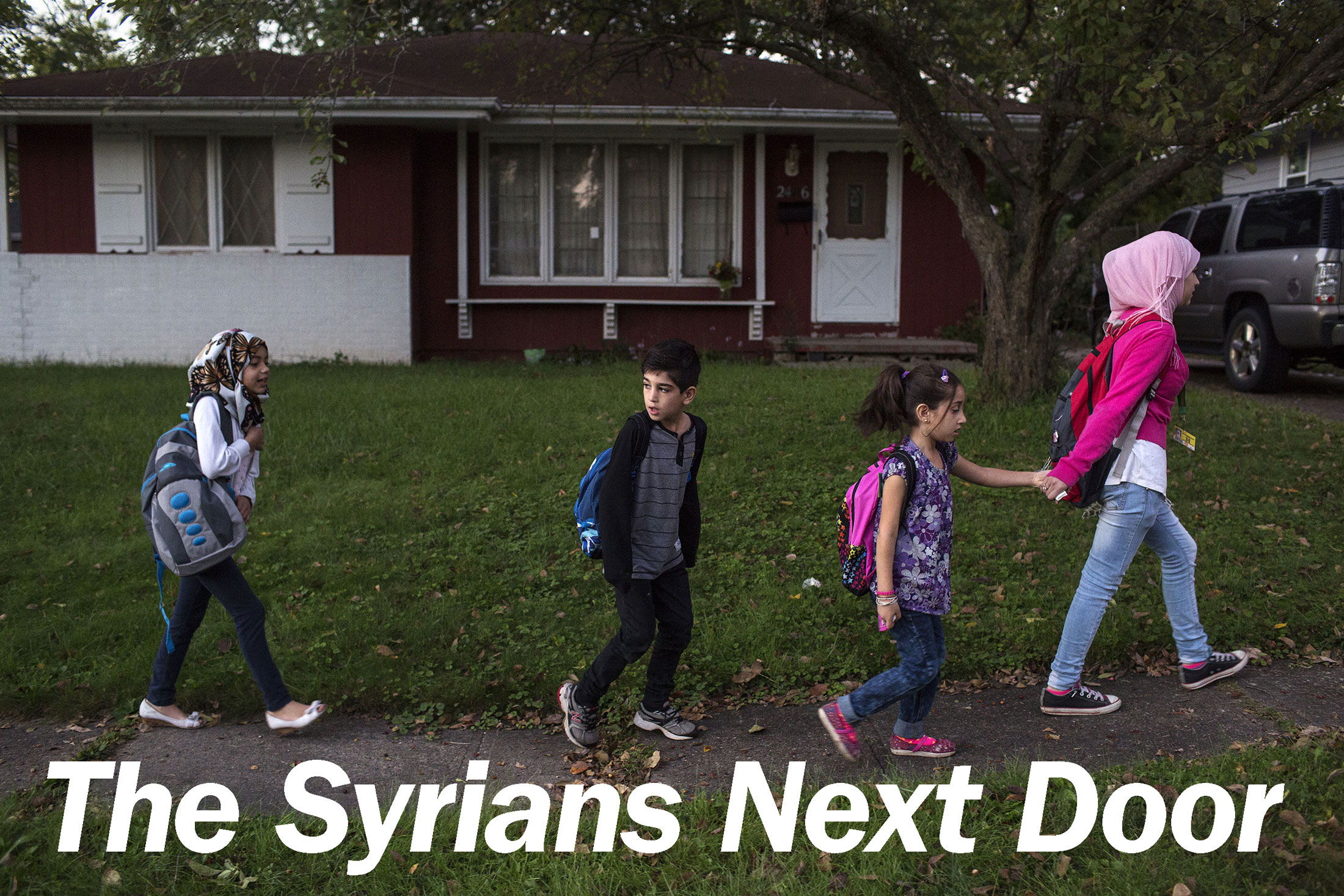 Sedra walks her brother Mutaz, sister Hala (with pink backpack) and a friend to their school-bus stop in the family's neighborhood in Des Moines.