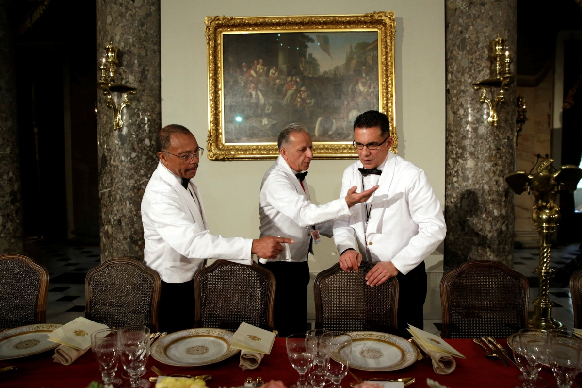 Waiters make final checks of a table prepared for President Trump and members of Congress before the Inaugural Luncheon in Statuary Hall on Capitol Hill in Washington, D.C., on Jan. 20, 2017.