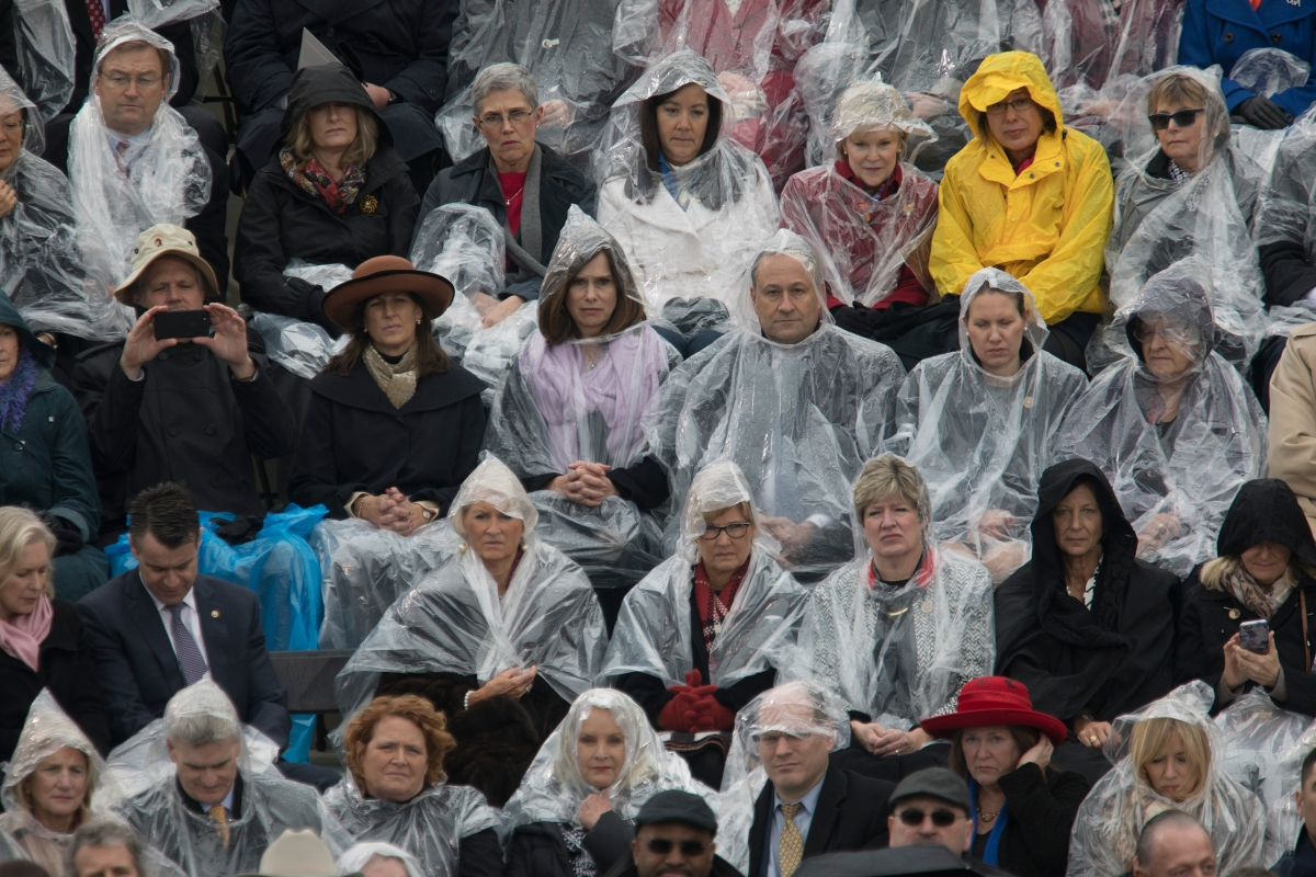 Attendees of President Trump's inauguration ceremony sit in the rain on Capitol grounds in Washington, D.C., on Jan. 20, 2017.