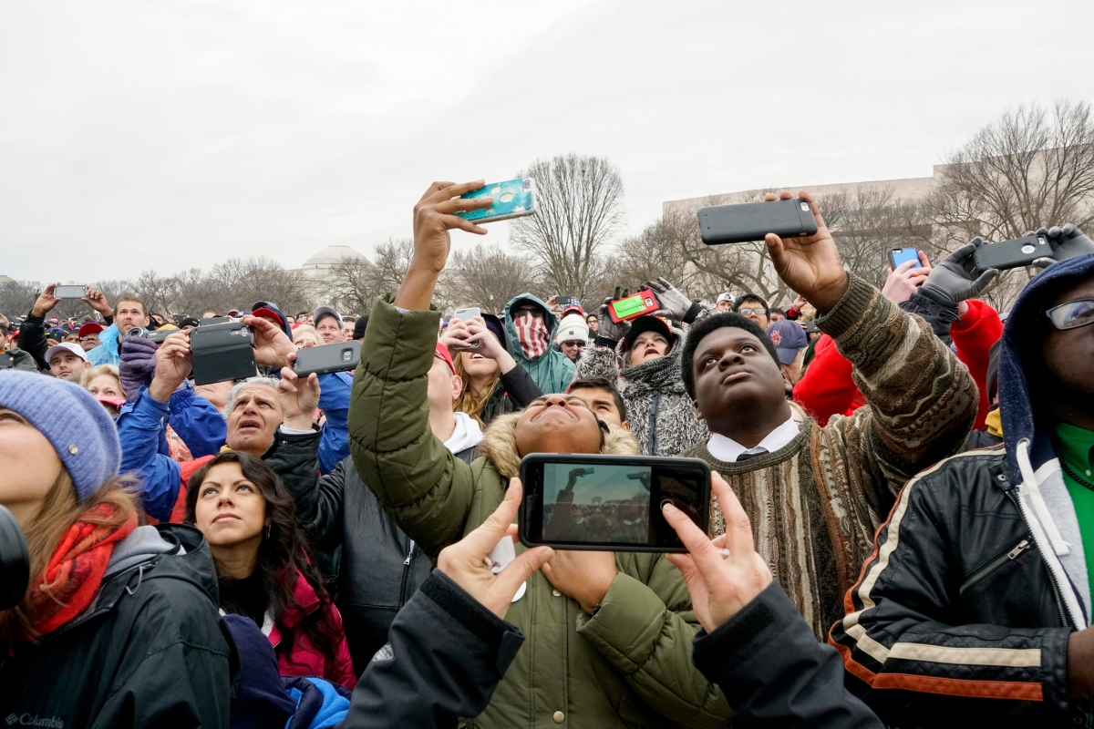 A woman who just got a glimpse of former First Lady Michelle Obama on a giant television screen reacts in a crowd of attendees during President Donald Trump's inauguration ceremony in Washington, D.C., on Jan. 20, 2017.