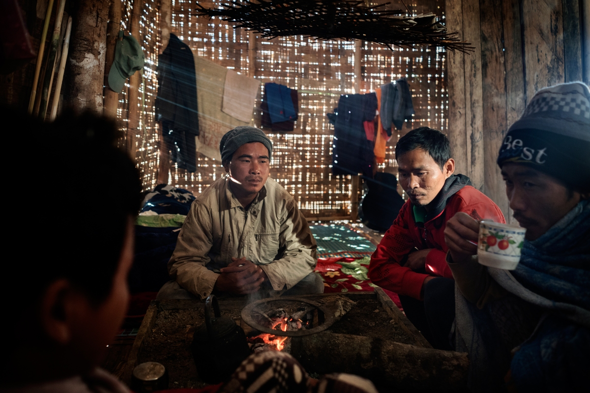 Hkawng Lum, second from right, a miner and heroin addict from Hpakant who worked in the mines for 10 years, warms himself by the fire at a rehabilitation facility near Myitkyina.