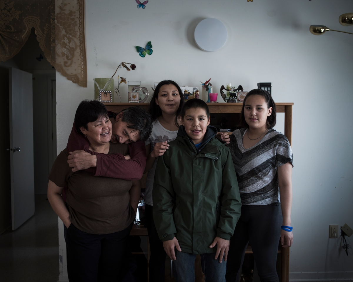 The Natanine family inside their living room in Clyde River, Nunavut. Christine Natanine (left) runs Ilisaqsivik, which offers counseling and mental health care to Inuit residents. Her husband, Jerry Natanine, (second from left) is the former mayor of Clyde River, and one of the most vocal proponents of protecting indigenous ways of life in the community.
