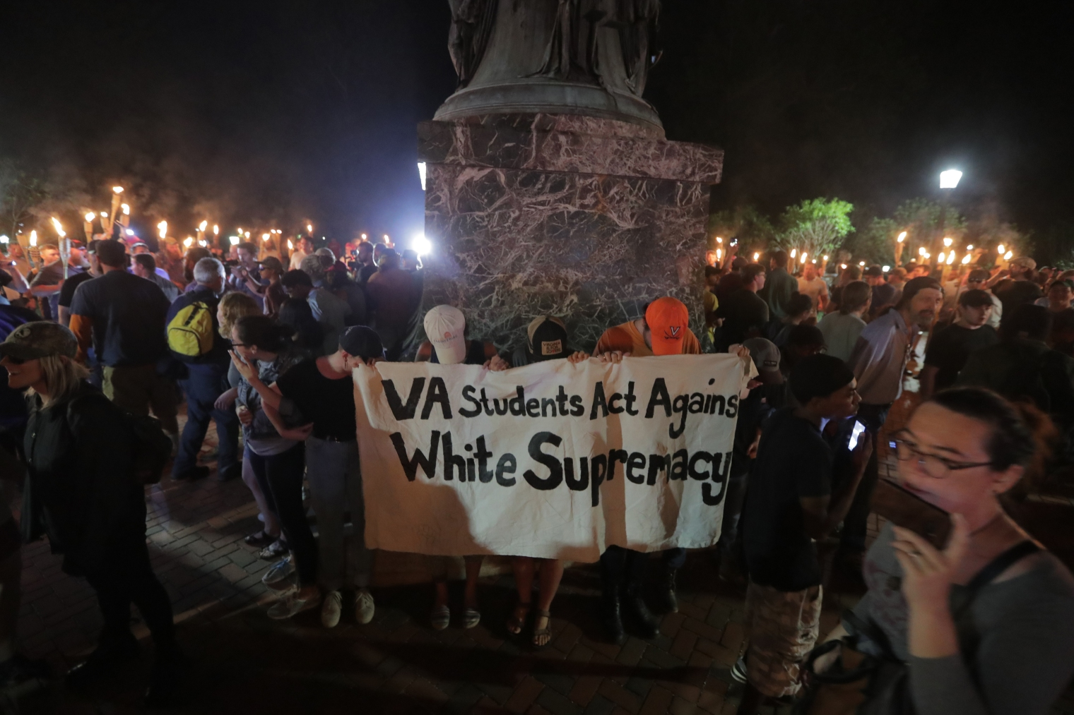 A group of counter-protesters against the white nationalists who gathered on the University of Virginia campus stand at the base of a Thomas Jefferson statue in Charlottesville, Va., on Aug. 11, 2017.