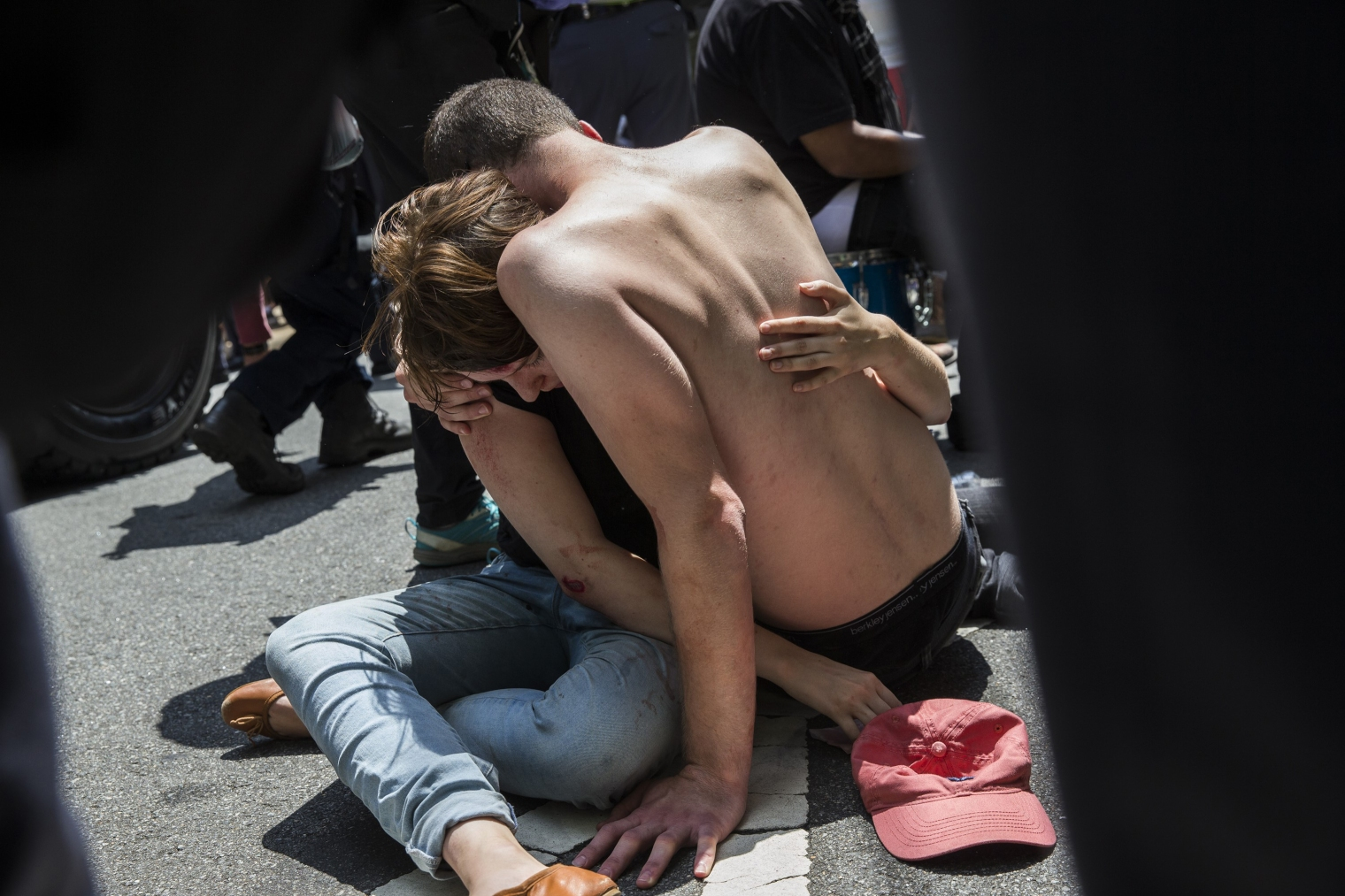 A man embraces an injured woman after a car rammed into a crowd of anti-white nationalist protesters in Charlottesville, Va., on Aug.12, 2017.